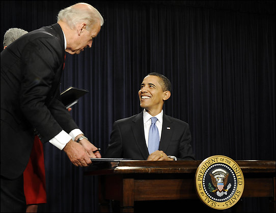President Obama, with Vice President Biden, finishes signing one of his executive orders on his first full day in office.